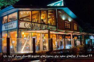نمای یک رستوران به صورت تقریبا شیشه ای و نور پردازی آن با چراغ های زرد و سفید در شب