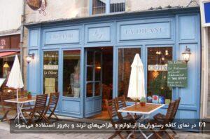 نمای یک کافه رستوران به رنگ آبی روشن با میز و صندلی های چوبی جلوی رستوران
