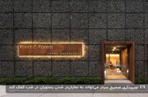 نمای سنگی یک رستوران با تقسیم بندی مربعی به همراه تابلو سردر ساده با نورپردازی طلایی دورش