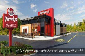 نمای رستوران به رنگ قرمز و مشکی در یک محوطه باز به همراه تعدادی درخت