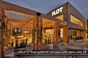 نمای چوبی یک رستوران به همراه محوطه ای با سقفی به سبک پرگولا و نورپردازی زیبا