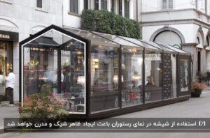 نمای کاملا شیشه ای یک رستوران مکعبی کنار یک ساختمان سفید و میز و صندلی های داخل رستوران