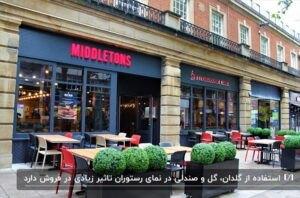 نمای یک رستورانی مشکی با نوشته های سردر قرمز به همراه فلاورباکسها و میز و صندلیها