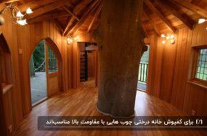 فضای داخلی یک خانه درختی با کفپوش چوبی، تنه ی درخت و چند چراغ روشن