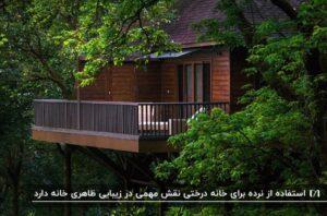 یک خانه درختی محصور در شاخه و برگ درختان دارای یک تراس حفاظ دار