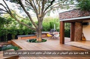 محوطه حیاطی با کفپوش چوبی، باربیکیو، میز گرد و چهار صندلی و یک درخت وسط کفپوش
