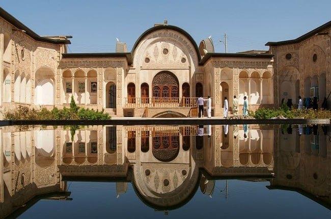 یک ساختمان قدیمی ایرانی با نمای کلاسیک و انعکاس تصویر آن روی آب استخر جلوی آن