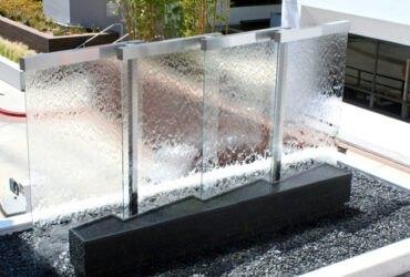 یک آب نمای شیشه ای با طراحی چند قسمتی روی یک پایه مشکی