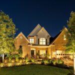 نورپردازی محوطه ی یک خانه با نمای آجری و حیاط چمنی